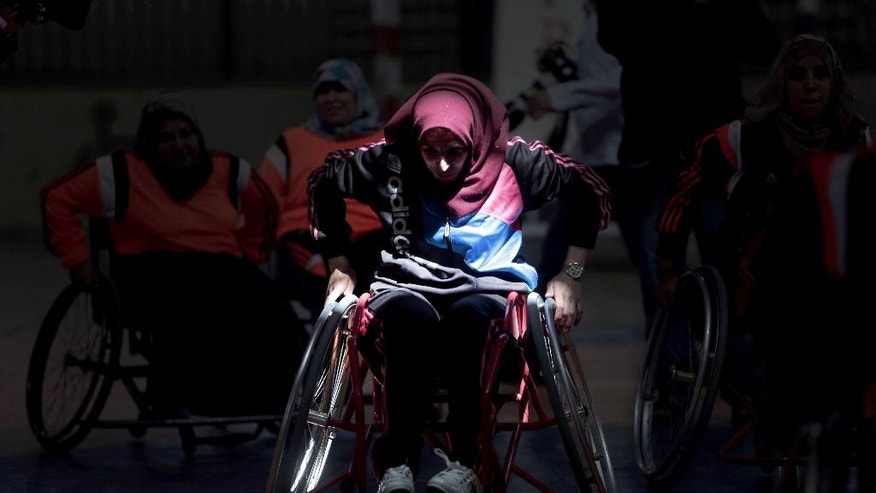 In this Saturday, May 28, 2016 photo, a disabled Palestinian woman takes part in a basketball training session for the territory's first female wheelchair basketball team in the Khan Younis refugee camp, southern Gaza Strip. In 2015, the International Committee of the Red Cross brought top U.S. coach Jess Markt. to Gaza to train local referees and coaches. Now, he is back to train players and organize tournaments between wheelchair teams. (AP Photo/Khalil Hamra)