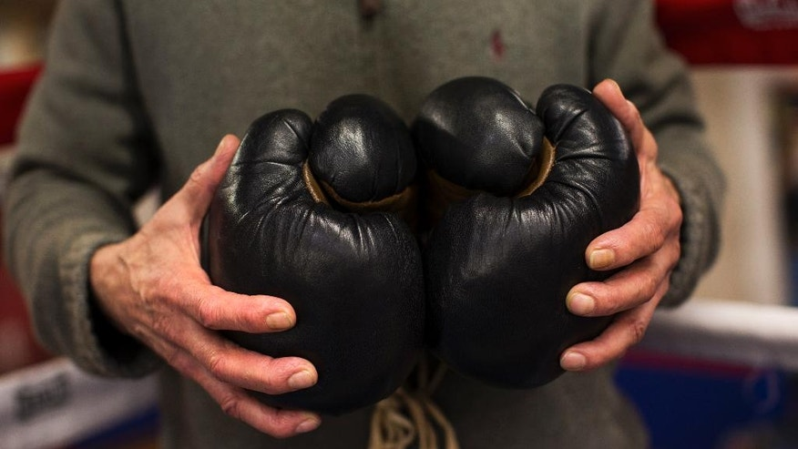 In this Friday, April 29, 2016 photo, boxing coach Manolo del Rio holds a pair of old style boxing gloves at El Rayo boxing gym in Madrid, Spain. At 84, Manolo del Rio is something of a legend in Spanish boxing circles, having spent more than 65 years training some of the country's best fighters and pledging to keep on going until he drops. (AP Photo/Francisco Seco)