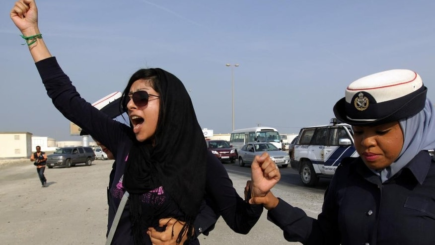 "FILE -- In this Oct. 21, 2012 file photo, Bahraini opposition activist Zainab al-Khawaja, left, gestures as she shouts ""God is greater than any tyrant,"" while being arrested by police officers in Eker, Bahrain. On Tuesday, May 31, 2016, Bahraini authorities released prominent rights activist Zainab al-Khawaja on humanitarian grounds after two and a half months behind bars. A dual Danish-Bahraini citizen, she was detained on March 14, 2016 and faced three years in prison on charges related to her participation in anti-government protests, including tearing up pictures of Bahraini King Hamad bin Isa Al Khalifa. (AP Photo/Hasan Jamali, File)"