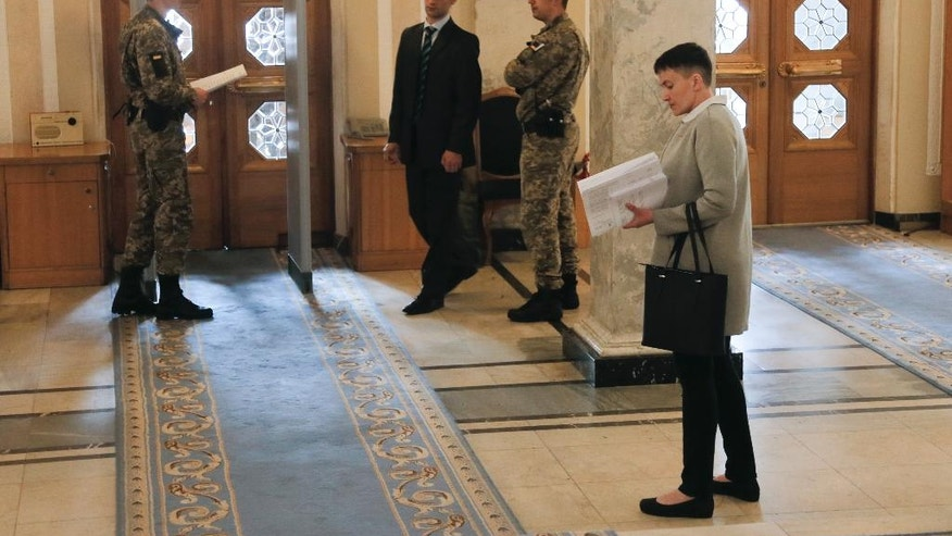 Ukrainian pilot Nadiya Savchenko holds agenda papers in the Ukrainian parliament in Kiev, Ukraine, Tuesday, May 31, 2016. Savchenko appeared for her first session at the Ukrainian parliament as a lawmaker in former Prime Minister Yulia Tymoshenko's party on Tuesday. (AP Photo/Efrem Lukatsky)