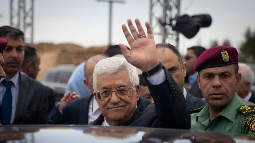 Palestinian President Mahmoud Abbas waving to journalists.