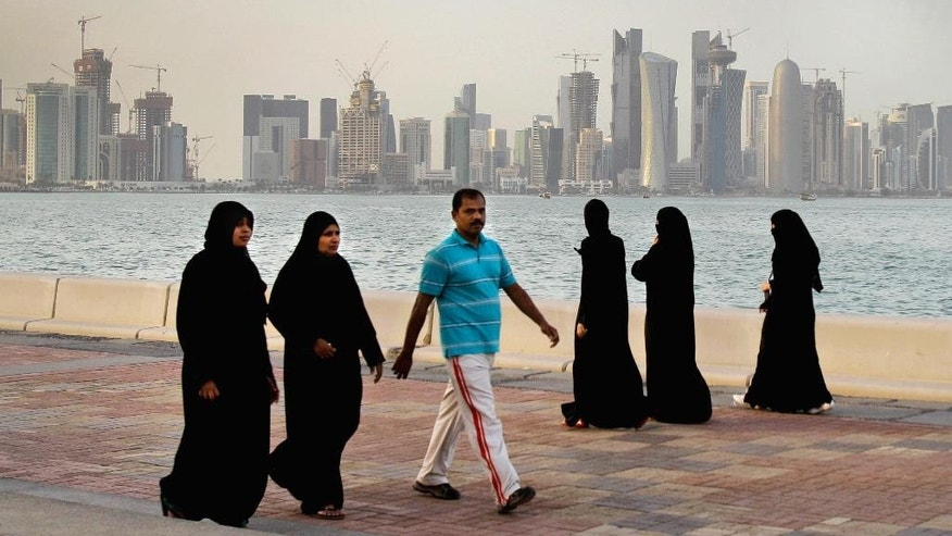 FILE- In this Saturday, April 7, 2012 file photo, with the new high-rise buildings of downtown Doha, background, Qatari women and a man walk by the sea in Doha, Qatar. The economic slowdown gripping countries across the Persian Gulf can be seen in layoffs, slowed construction projects and government cutbacks. For the millions of foreign workers drawn by brighter job prospects, it can have a far-darker side if they find themselves deep in debt.  (AP Photo/Kamran Jebreili, File)