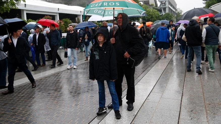 People wait under umbrella as rain delays matches at the French Open tennis tournament at the Roland Garros stadium, Tuesday, May 31, 2016 in Paris. (AP Photo/Christophe Ena)