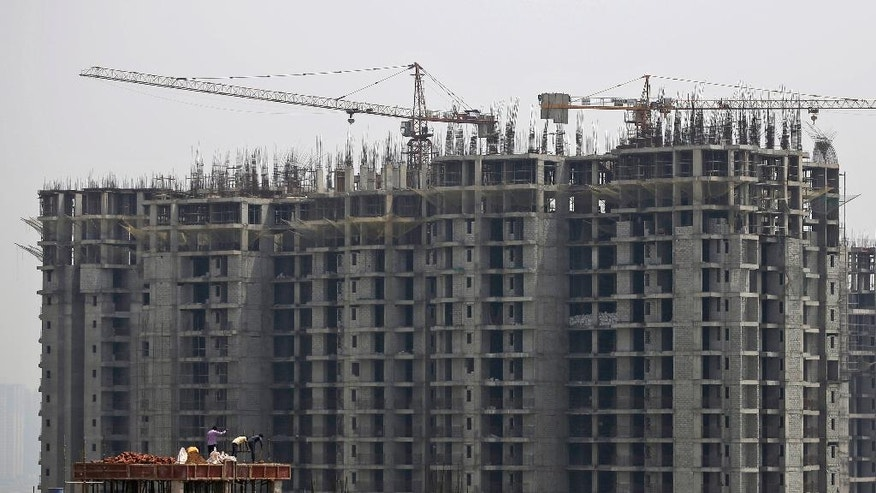 Laborers work at a construction site of high rise residential complex in Noida, a suburb of New Delhi, India, Tuesday, May 31, 2016. The UN's mid-2016 report on the World Economic Situation and Prospects released earlier this month expects India to grow by 7.3 per cent this year and 7.5 per cent next year, the strongest GDP growth rate for a large economy, despite the drought affecting millions of people in various states. (AP Photo/Altaf Qadri)