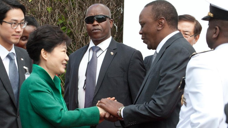 South Korea's president Park Geun-hye, centre left, is greeted by Kenyan President, Uhuru Kenyatta, centre right, at Nairobi State House Nairobi, Kenya, Tuesday May 31, 2016.  South Korea's president has arrived in Kenya for a two-day state visit during which she is expected to discuss business and trade opportunities, the first such visit by a South Korean president. (AP Photo/Sayyid Abdul Azim)