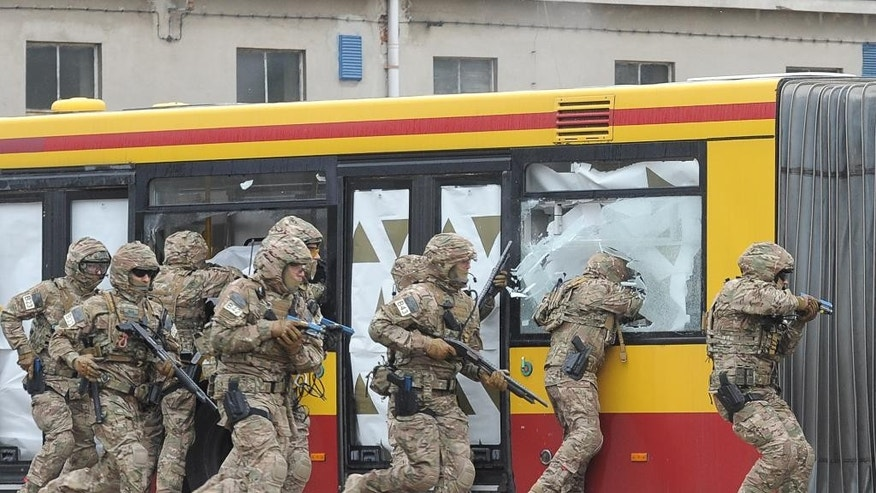 Members of the Polish Army military police anti terrorist squad train freeing hostages from a hijacked bus, at a bus depot in Warsaw, Poland, Tuesday, May 31, 2016. The excercise was a part of preparations for the upcoming NATO summit in Warsaw in July. (AP Photo/Alik Keplicz)