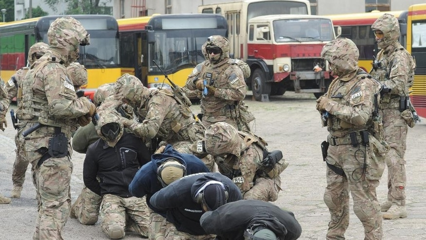 Members of the Polish Army military police anti terrorist squad train detaining 'hijackers', at a bus depot in Warsaw, Poland, Tuesday, May 31, 2016. The excercise was a part of preparations for the upcoming NATO summit in Warsaw in July. (AP Photo/Alik Keplicz)