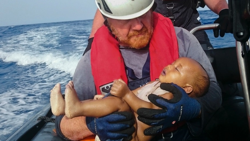 May 27, 2016: A Sea-Watch humanitarian organization crew member holds a drowned migrant baby, during a rescue operation off the coasts of Libya. (AP)