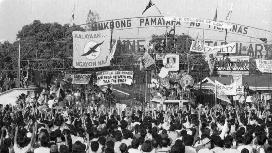 "FILE - In this Feb. 24, 1986 file photo, people pour in the street leading to the suburban military camp where rebel soldiers held a mutiny that culminated in the four-day ""People Power"" revolt.  Leni Robredo was a college student three decades ago when she rose with multitudes of Filipinos in a largely peaceful revolt that ousted Ferdinand Marcos as the world watched in awe. Now a neophyte 52-year-old politician, Robredo defeated Sen. Ferdinand Marcos Jr., son and namesake of the late dictator, in a cliffhanger race for vice president in May, 2016. (AP Photo/File)"