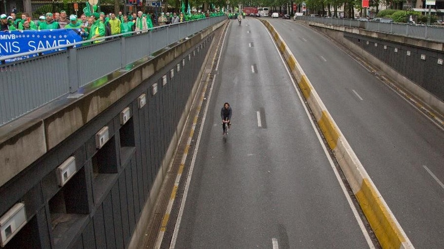 Two cyclists ride into an empty tunnel as protestors march during a demonstration against proposed working regulations in Brussels on Tuesday, May 31, 2016. Public sector employees are striking throughout Belgium, disrupting train and bus service and affecting schools, prisons and delivery of the mail. (AP Photo/Virginia Mayo)