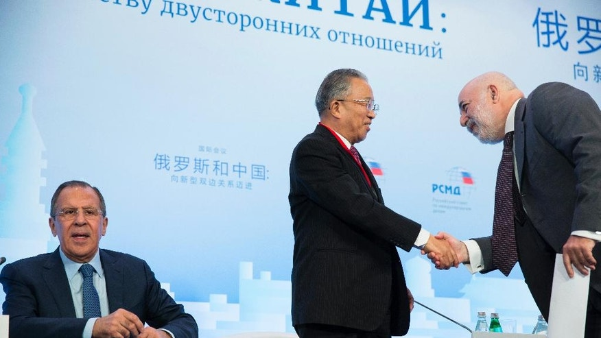 Chairman of the Chinese Chapter of the Russian-Chinese Committee of Friendship, Peace and Development Dai Bingguo, center, shakes hands with Russian businessman Viktor Vekselberg, as Russian Foreign Minister Sergey Lavrov, left, attends the Russian International Affairs Council in Moscow, Russia, Tuesday, May 31, 2016. The Russian International Affairs Council hosts a Russia-China conference ahead of Russian President Vladimir Putin's official visit to China in June. (AP Photo/Pavel Golovkin)