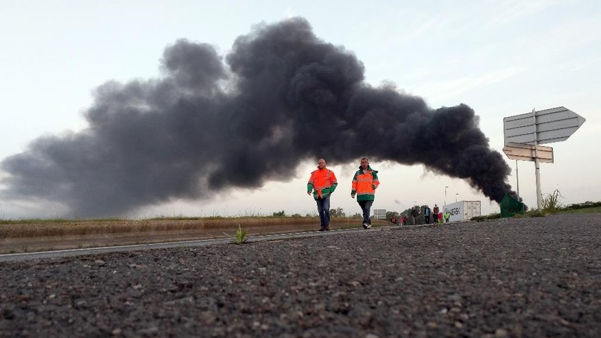 FILE - This Thursday, May 26, 2016 file photo shows two union activists in fluorescent vests walking toward the Normandie Bridge outside of Le Havre, western France, during a blockade action. The cloud of black smoke is from burning tires. The reforms, which are aimed at bringing extra flexibility to France's arthritic job market, have led to nationwide fuel shortages, blocked bridges and mass protests. (AP Photo/Raphael Satter, File)