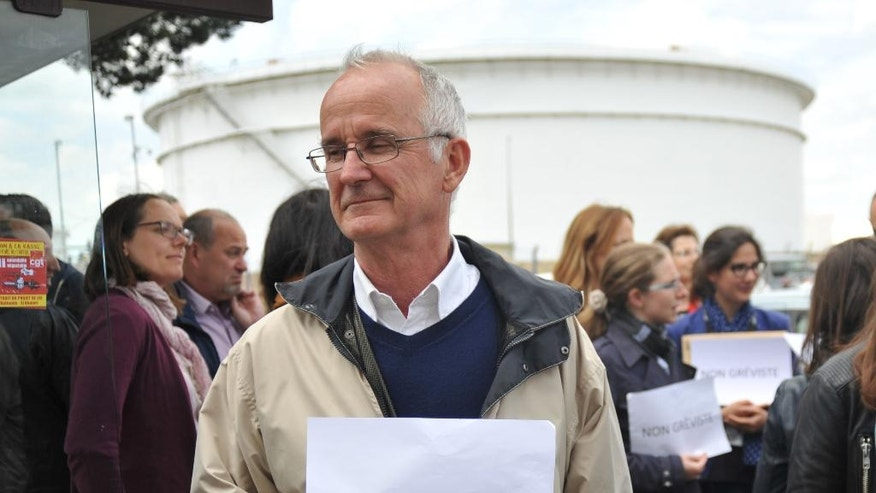 "FILE - This Wednesday, May 25, 2016 file photo shows Etienne Hubault holding a paper that reads ""non-striker"" during a gathering outside the Notre-Dame-de-Gravenchon refinery, where union workers were discussing a possible work stoppage, in Notre-Dame-de-Gravenchon, western France. The reforms, which are aimed at bringing extra flexibility to France's arthritic job market, have led to nationwide fuel shortages, blocked bridges and mass protests. (AP Photo/William Wilson Lewis III, File)"