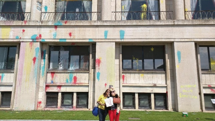 In this photo dated Thursday, May 26, 2016, two women pose for a selfie in front of Le Havre's paint-splattered City Hall, western France, following a rally against France's disputed labor reforms. The reforms, which are aimed at bringing extra flexibility to France's arthritic job market, have led to nationwide fuel shortages, blocked bridges and mass protests. (AP Photo/Raphael Satter)