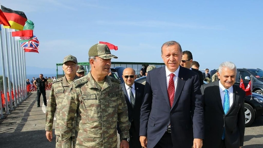 Turkey's President Recep Tayyip Erdogan, center, and Prime Minister Binali Yildirim, right, and Chief of Staff Gen. Hulusi Akar arrive to observe EFES 2016, Turkey's largest military exercise with multifaceted operations, including air and amphibious assaults, in Seferihisar near Izmir, Turkey. Tuesday, May 31, 2016. (Kayhan Ozer, Presidential Press Service/Pool via AP)