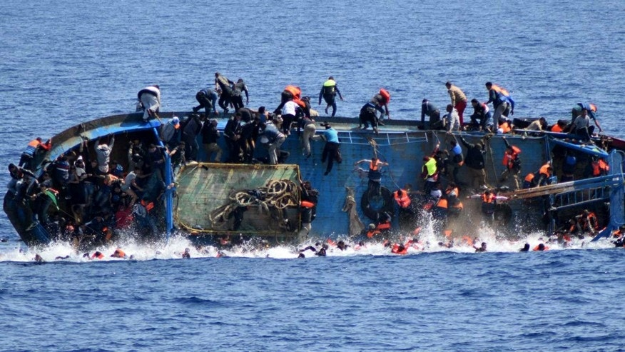 In this May 25, 2016 file photo made available by the Italian Navy, people try to jump in the water right before their boat overturns off the Libyan coast.