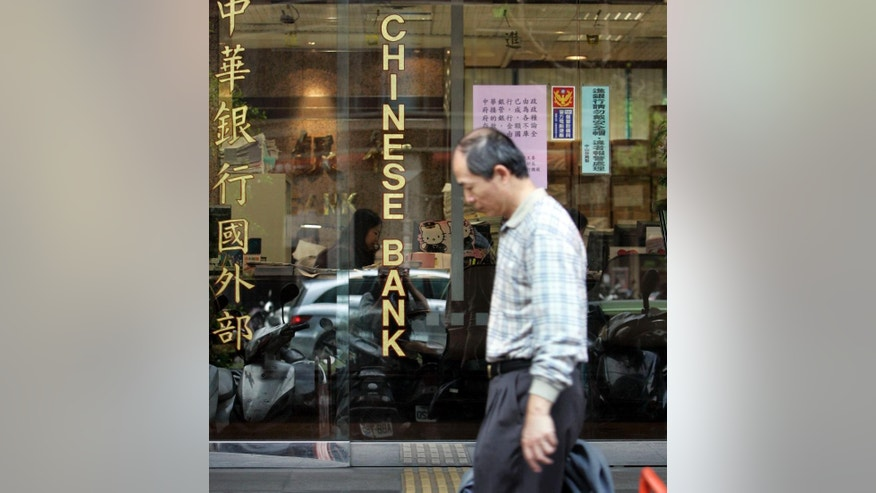 FILE - In this file photo from Jan. 16, 2007, a pedestrian passes by a branch of The Chinese Bank, a subsidiary of the financially troubled Rebar Asia Pacific Group in Taipei, Taiwan. Taiwan's foreign ministry has confirmed a report that a former tycoon a founder of the Rebar Asia Pacific Group Wang You-theng wanted on allegations of embezzlement and fraud was killed in a car accident in California. He had been hiding for years in the United States. (AP Photo/Wally Santana, FIle )