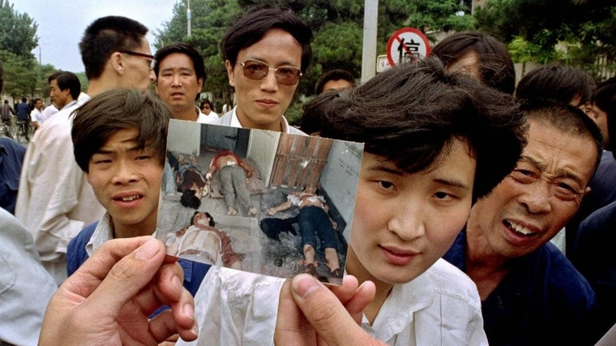 "FILE- In this file photo take June 5, 1989, people on Chang'an Boulevard hold up a photo that they described as dead victims of the violence against pro-democracy protesters on Tiananmen Square, Beijing. Hundreds had been killed in the early morning hours of June 4, in clashes with Chinese soldiers. Mothers of some of those killed in the bloody crackdown on China's 1989 Tiananmen pro-democracy movement say they have lived through 27 years of state-led ""terror and suffocation"" and vow to continue pushing for the truth ahead of this weekend's anniversary of the events. (AP Photo/Jeff Widener, FIle)"