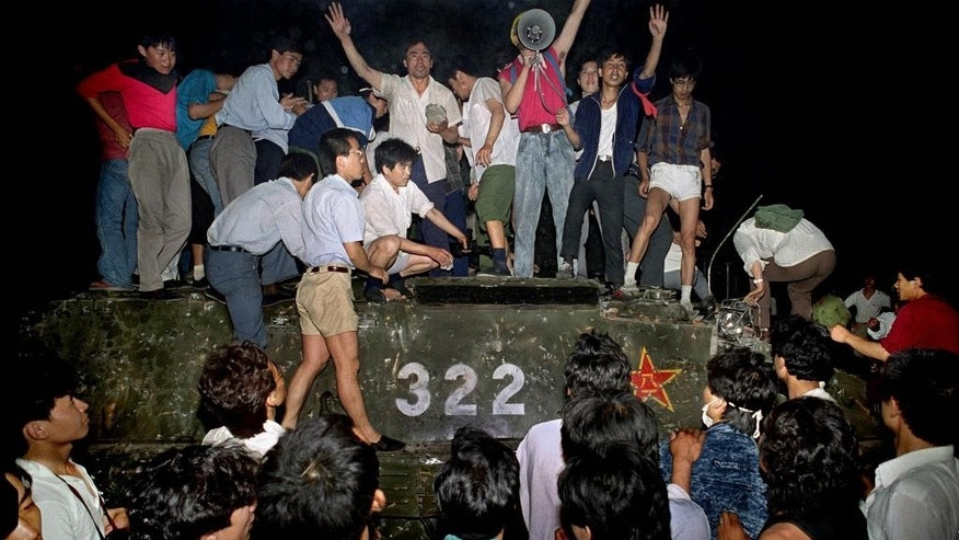 "FILE - In this file photo taken on June 4, 1989, civilians hold rocks as they stand on a government armored vehicle near Chang'an Boulevard in Beijing. Violence escalated between pro-democracy protesters and Chinese troops, leaving hundreds dead overnight. Mothers of some of those killed in the bloody crackdown on China's 1989 Tiananmen pro-democracy movement say they have lived through 27 years of state-led ""terror and suffocation"" and vow to continue pushing for the truth ahead of this weekend's anniversary of the events. (AP Photo/Jeff Widener, File)"