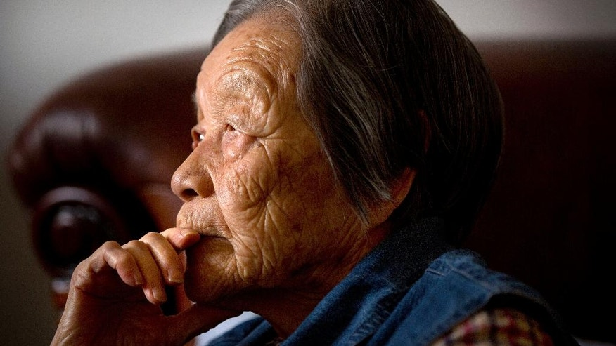 In this Tuesday, May 17, 2016 photo, Cheng Bi, a 93-year-old retired Beijing school administrator, pauses during an interview at her home in Beijing. Cheng was abused by many students but believes two students — whose names she still remembers — should have apologized for their particularly brutal acts against her during the Cultural Revolution. One is dead, and she does not expect the other to apologize. (AP Photo/Mark Schiefelbein)