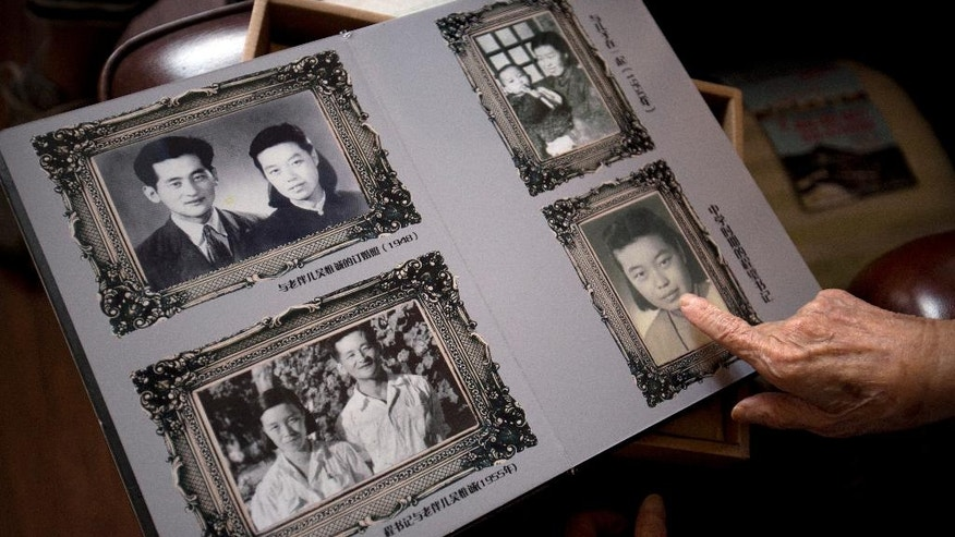 In this Tuesday, May 17, 2016 photo, Cheng Bi, 93, points out a photo of herself from the 1940s in a photo album at her home in Beijing. Cheng, a 93-year-old retired Beijing school administrator, was abused by many students but believes two students — whose names she still remembers — should have apologized for their particularly brutal acts against her during the Cultural Revolution. One is dead, and she does not expect the other to apologize. (AP Photo/Mark Schiefelbein)