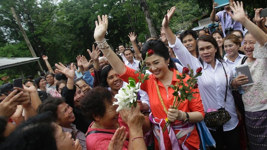 In this May 30, 2016 photo, Thailand's former prime minister Yingluck Shinawatra meets with fans in Bueng Kan Province, Thailand. As the former prime minister made her way through a line of fans, some cried, others screamed and a few embraced her. This was not a political campaign stop. If it had been, the generals who ousted Yingluck two years ago never would have let it happen. (AP Photo/Sakchai Lalit)