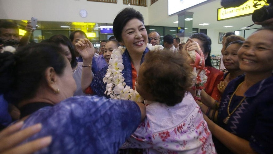 In this May 30, 2016 photo, Thailand's former prime minister Yingluck Shinawatra gets a hug from a supporter in Sakon Nakhon province, Thailand. As the former prime minister made her way through a line of fans, some cried, others screamed and a few embraced her. This was not a political campaign stop. If it had been, the generals who ousted Yingluck two years ago never would have let it happen. (AP Photo/Sakchai Lalit)