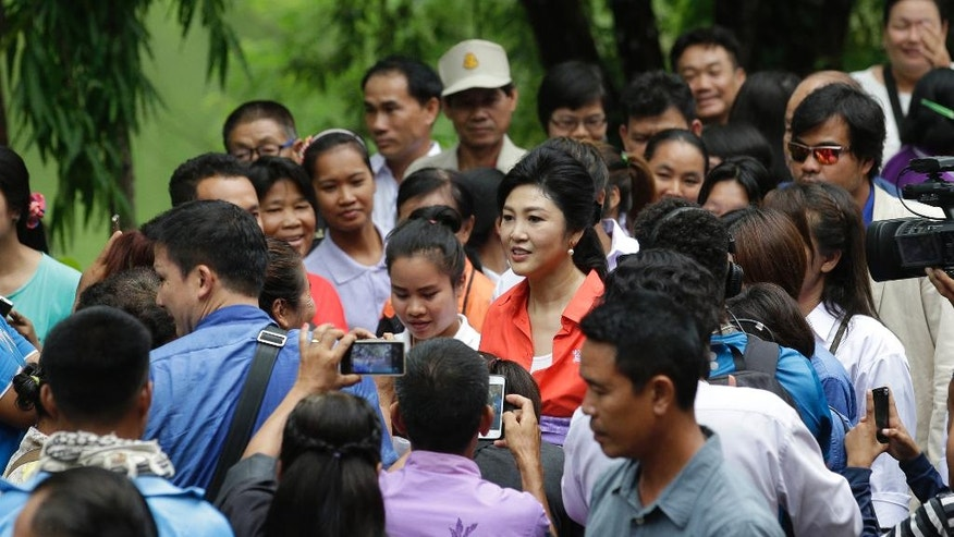 In this May 30, 2016 photo, Thailand's former prime minister Yingluck Shinawatra is greeted by supporters as she arrives at Bueng Kan Province, Thailand. As the former prime minister made her way through a line of fans, some cried, others screamed and a few embraced her. This was not a political campaign stop. If it had been, the generals who ousted Yingluck two years ago never would have let it happen. (AP Photo/Sakchai Lalit)