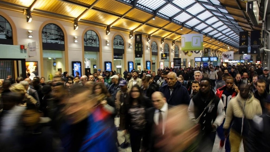Commuters head to one of the few trains running after a strike stars at the Gare Saint Lazare train station, in Paris, Wednesday, June 1, 2016. Workers at the SNCF national rail authority, whose train service will be crucial to Euro 2016 spectators, are on an open-ended strike to protest their working conditions and a controversial government labor reform. (AP Photo/Markus Schreiber)