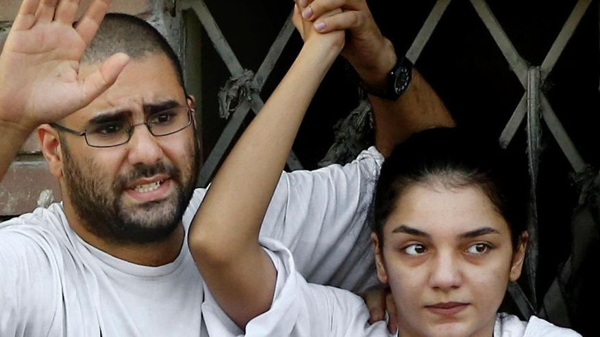 """FILE - In this Thursday, Aug. 28, 2014 file photo, Surrounded by plainclothes policemen, Egyptian prominent blogger Alaa Abdel-Fattah, left, speaks to the crowd after attending, with his sister Sanaa, right, their father Ahmed Seif funeral in Cairo, Egypt. When 22-year-old Sanaa was summoned for questioning on accusations of inciting protests, she refused to answer the investigating judge's questions. She told him she would not participate in the """"charade"""" and said the courts and prosecutors all follow the will of the government. On May 14, 2016 Sanaa gave herself up to authorities and is now serving her sentence in a prison just outside Cairo. (AP Photo/Hassan Ammar, File)"""