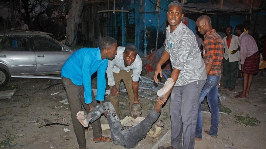 Somali men carry a wounded civilian who was injured in a bomb attack on an hotel in Mogadishu, Somalia Wednesday, June 1, 2016. The attack took place on the Ambassador hotel, which is often frequented by government officials and business executives. (AP Photo/Farah Abdi Warsameh)