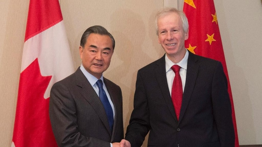 "Chinese Foreign Minister Wang Yi, left, and Canadian Foreign Affairs Minister Stephane Dion pose for photographers in Parliament Hill in Ottawa, Ontario, Wednesday, June 1, 2016. Wang publicly berated a Canadian journalist on Wednesday for asking a question about his country's human rights record.  Wang said it was ""irresponsible"" of a journalist from the web outlet IPolitics to ask about human rights and the jailing of a Canadian, Kevin Garratt, who is charged with espionage. (Adrian Wyld /The Canadian Press via AP) MANDATORY CREDIT"