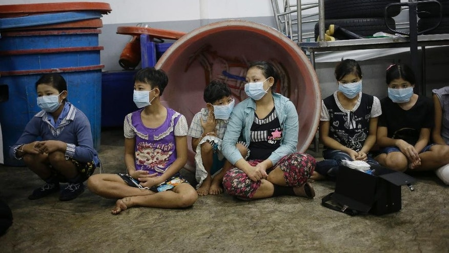 FILE - In this file photo taken Nov. 9, 2015, children and teenagers sit together to be registered by officials during a raid on a shrimp shed in Samut Sakhon, Thailand. On Tuesday a global slavery index puts India at the top of the list with the world's highest number of bonded and child laborers, far more than in second-place China. (AP Photo/Dita Alangkara, File)