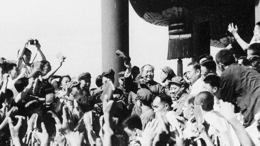 FILE - In this August 1966, file photo, Chinese leader Chairman Mao Zedong, center, waves as he meets with teachers and students from Beijing and other parts of China, in Beijing. A time of massive upheaval, violence and chaos, China's 1966-1976 Cultural Revolution, was launched 50 years ago by Communist Party leader Mao, who began it by purging officials considered insufficiently loyal. Over its course longstanding party officials, intellectuals and teachers came under violent attack, while traditional Chinese thought and culture were condemned along with foreign influences. (Photo via AP, File)