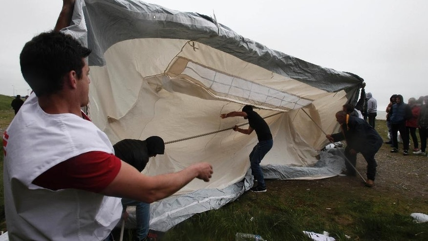 A member of the international medical charity, left, known by its French acronym MSF in a new makeshift camp along the storm-hit cliffs near the port of Dieppe, northern France, Wednesday, June 1, 2016. A group of around 150 Albanian migrants set up camp near the English channel hoping to cross to the UK. (AP Photo/Michel Spingler)