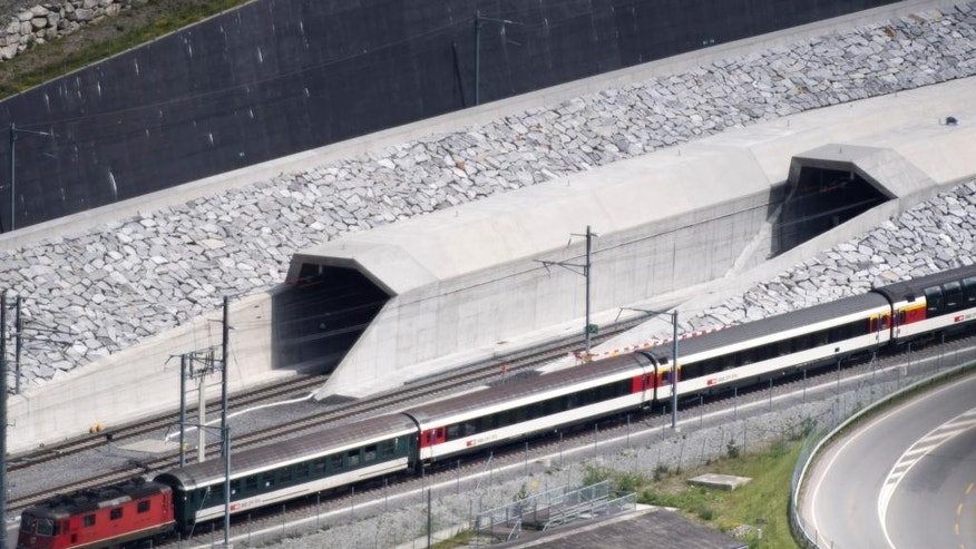 FILE- In this Tuesday, May 31, 2016 file photo, a train passes in front of the northern portal of the Gotthard Base Tunnel on the eve of its inauguration, in Erstfeld, Canton of Uri, Switzerland. Just like Hannibal in ancient times, Swiss engineers have conquered the Alps burrowing the world's longest railway tunnel to ease trade and congestion in European trade and travel. (Laurent Gillieron/Keystone via AP)
