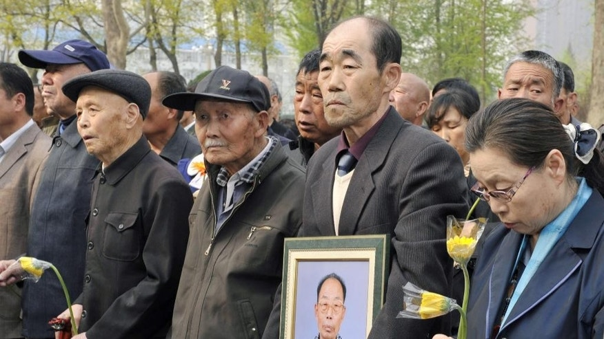In this April 2, 2014 photo, Chinese forced laborers, second and third from left, and bereaved families stand during a memorial gathering before suing a file against Mitsubishi Materials Corp. in front of High People's Court in Shijiazhuang, China's Hebei Province. Mitsubishi Materials Corp., one of dozens of Japanese companies that used Chinese forced laborers during World War II, reached a settlement, its first ever involving forced laborers, Wednesday, June 1, 2016, with Chinese victim groups that includes a company apology and compensation. (Kyodo News via AP) JAPAN OUT, CREDIT MANDATORY