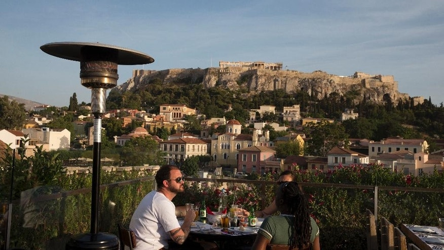 In this Tuesday, May 31, 2016 photo, tourists eat at a restaurant- cafe bar in front of the ancient Acropolis hill in central Athens. Greeks have woken up to a new wave of price hikes that have been demanded in return for more international bailout loans, with the highest increases targeting the main ingredients of the country's cafe culture: Coffee and beer.(AP Photo/Petros Giannakouris)