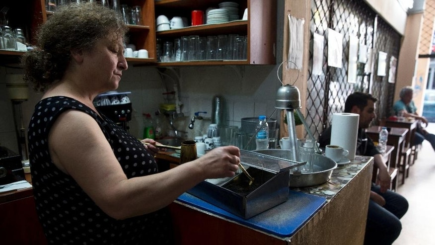 A woman makes a Greek coffee in a traditional coffee shop in central Athens, on Wednesday, June 1, 2016. Greeks have woken up to a new wave of price hikes that have been demanded in return for more international bailout loans, with the highest increases targeting the main ingredients of the country's cafe culture: Coffee and beer.(AP Photo/Petros Giannakouris)