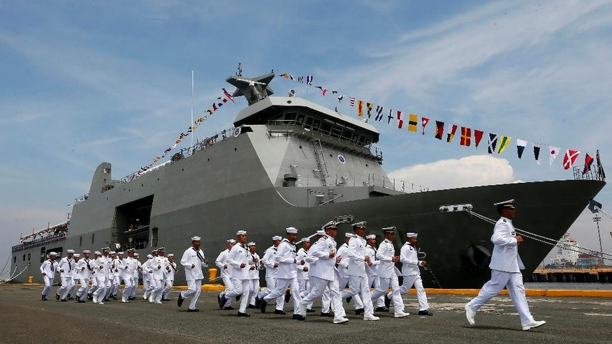 Crew of the new Philippine Navy Strategic Sealift Vessel BRP Tarlac (LD601) rush to board their vessel during the commissioning ceremony with three other vessels to coincide with the Philippine Navy's 118th anniversary Wednesday, June 1, 2016 at South Harbor in Manila, Philippines. The 7,200 ton ship is the country's largest to date and is capable of transporting personnel, equipment and aid during humanitarian assistance and disaster response operations. (AP Photo/Bullit Marquez)