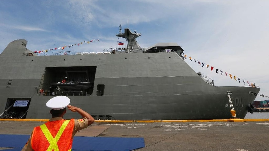 A Philippine Marine salutes during the commissioning ceremony for the new Philippine Navy Strategic Sealift Vessel BRP Tarlac (LD601) and three other vessels to coincide with the Philippine Navy's 118th anniversary Wednesday, June 1, 2016 at Manila's South Harbor in Manila, Philippines. The 7,200 ton ship is the country's largest to date and is capable of transporting personnel, equipment and aid during humanitarian assistance and disaster response operations. (AP Photo/Bullit Marquez)