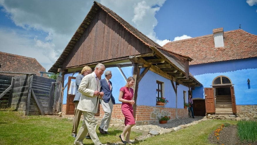 "Britain's Prince Charles is accompanied by Aura Woodward, right, the executive director of The Prince of Wales Foundation in the Transylvanian village of Viscri, Romania, Wednesday, June 1, 2016, during the opening of a training center to encourage conservation, farming and sustainable development in Romania. Charles, who has long been enamored of Romania's rural traditions, opened the ""The Prince of Wales's Training Centre"", which will bring skills and knowledge to rural communities.(AP Photo/Andreea Alexandru) ROMANIA OUT"