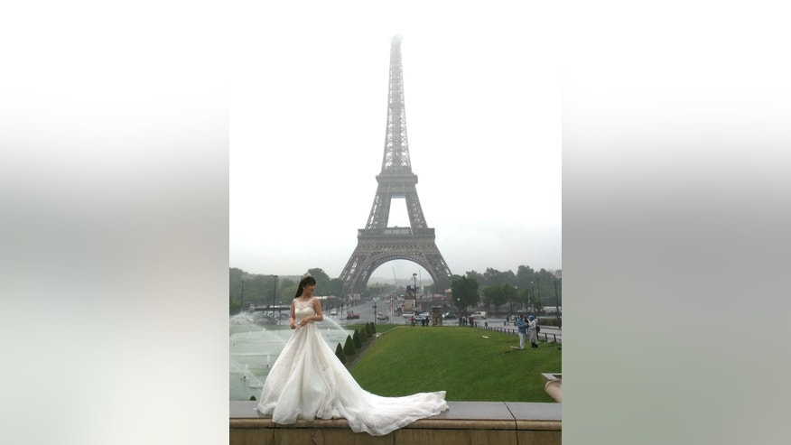 Bride-to-be Liu Yuan Yuan of China poses for photographs at the Trocardero gardens in Paris, France, Tuesday, May 31, 2016. Heavy precipitation has drenched parts of France, prompting flood warnings near the English Channel and causing more delays at the French Open. (AP Photo/Raphael Satter)