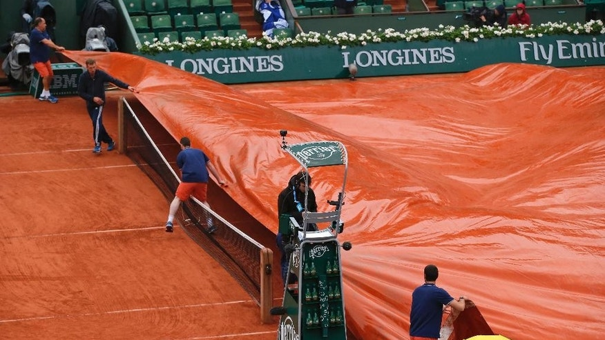 Stadium workers cover center court after rain suspended the fourth round match of the French Open tennis tournament between Serbia's Novak Djokovic and Spain's Roberto Bautista Agut at the Roland Garros stadium in Paris, France, Tuesday, May 31, 2016. (AP Photo/Michel Euler)
