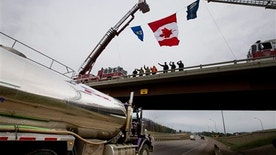 Firefighters and police welcome people into Fort McMurray, Canada on Wednesday June 1, 2016. Some residents were permitted to re-enter their homes after being evacuated due to wildfires.  Residents started to return to the fire-damaged city in northern Alberta on Wednesday, but officials have warned that they should not expect everything to be running normally right away. (Jason Franson/The Canadian Press via AP) MANDATORY CREDIT