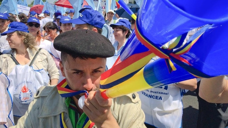 Aurel Selaru, a Romanian teachers union leader, blows a horn during a march in Bucharest, Romania, Wednesday, June 1, 2016. Thousands of Romanian teachers have demonstrated in Bucharest outside the government's main offices before marching through the capital to demand higher salaries. (AP Photo/Nicolae Dumitrache)