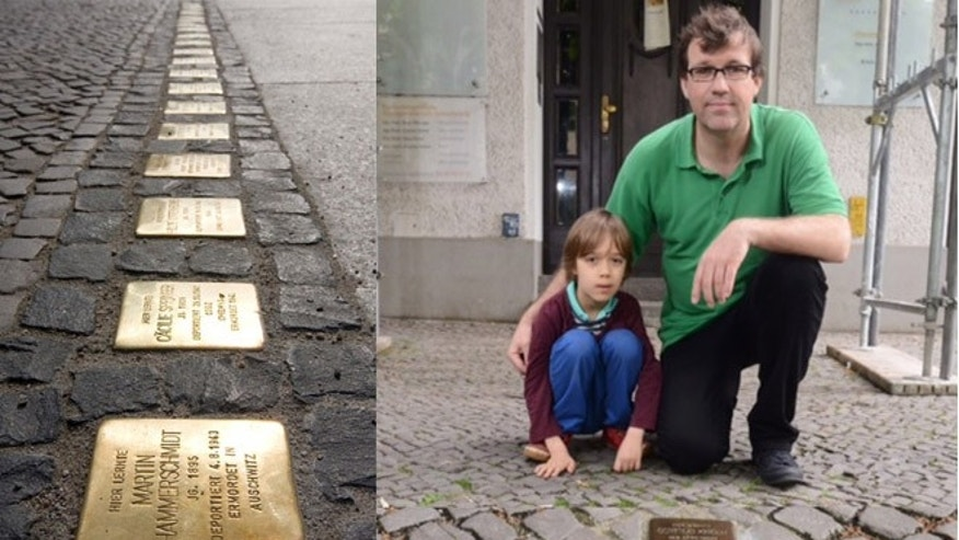 Markus Hesselmann and his son, Juri, view one of the plaques that commemorate victims of the Holocaust.
