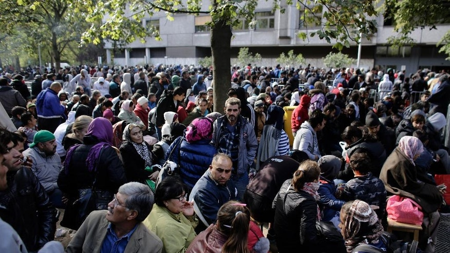 FILE - In this file photo taken Wednesday, Sept. 30, 2015, hundreds of migrants and refugees wait for Berlin's State Office of Health and Welfare,Lageso, the cities central registration point for asylum seekers in Berlin, Germany. Hundreds or more of Syrian refugees who want to return home are finding themselves trapped in Germany, often without their families. Some are going back illegally. (AP Photo/Markus Schreiber, file)