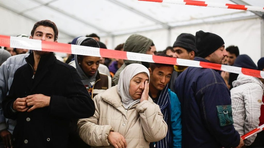 FILE - In this file photo taken Thursday, Oct. 15, 2015, migrants wait in exclusion zone for transport to a registration office at the State Office of Health and Welfare (LaGeSo) in Berlin, Germany. Hundreds or more of Syrian refugees who want to return home are finding themselves trapped in Germany, often without their families. Some are going back illegally. (AP Photo/Markus Schreiber, file)