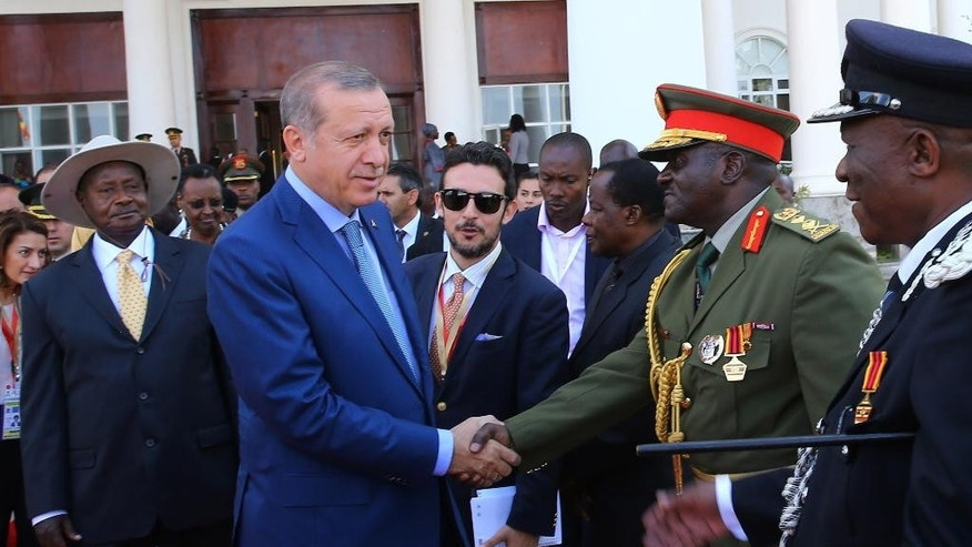 Uganda's long-time president Yoweri Museveni, left, watches as Turkey's President Recep Tayyip Erdogan shakes hands with Ugandan military generals during a welcome ceremony in the capital Kampala, Uganda, Wednesday, June 1, 2016. Museveni was sworn in earlier in May for a fifth term taking him into his fourth decade in power, amid arrests of opposition politicians and a shutdown of social media. Erdogan is on a two-day state visit.(Kayhan Ozer, Presidential Press Service/Pool via AP)